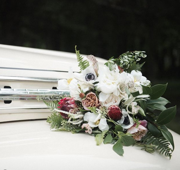 Wedding bouquet with protea, ranunculus and pitcher plants.